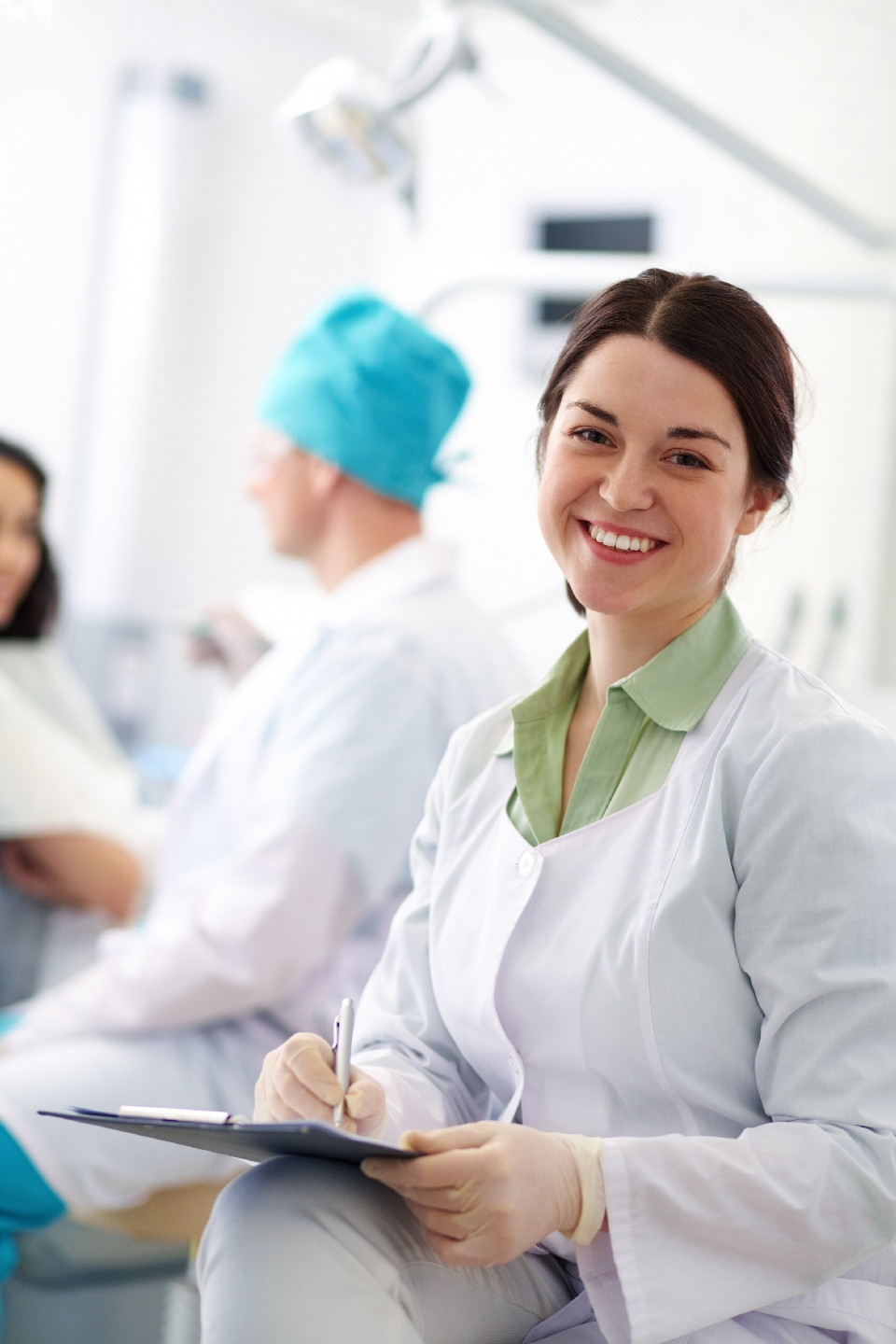 Smiling nurse with clipboard looking at camera on background of her colleague